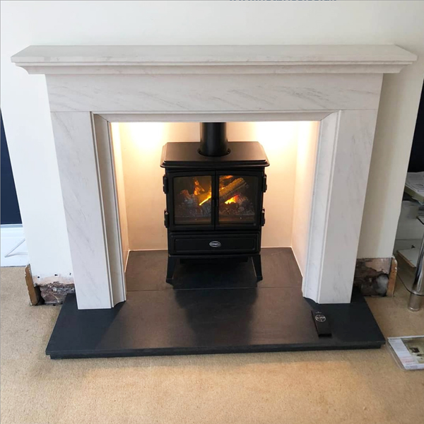 Limestone fireplace surround with electric stove in Manchester